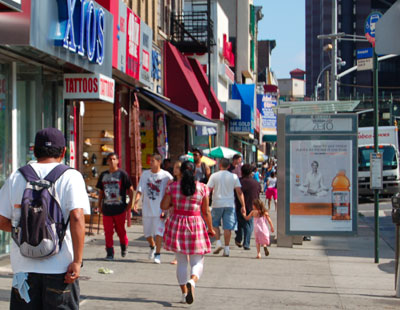 Shoppers walk south down Graham Ave in front of Xios